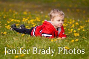 little boy lying in the grass by flowers
