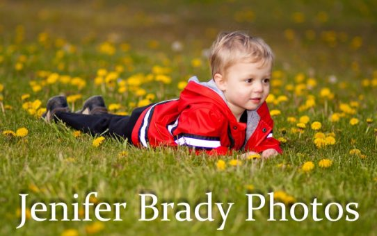 little boy lying in the grass by flowers